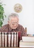 Hombre mayor en biblioteca Fotos de archivo libres de regalías