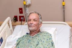 Hombre mayor en cama de hospital Imagen de archivo libre de regalías