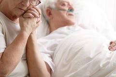 Hombre mayor en cama de hospital y su esposa que lleva a cabo su mano foto de archivo