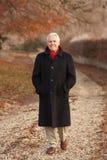 Hombre mayor en caminata del invierno con paisaje escarchado Imagen de archivo libre de regalías