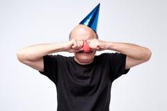 Hombre mayor en casquillo del cumpleaños que llora y que limpia los rasgones en su partido fotografía de archivo libre de regalías
