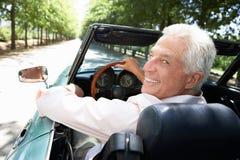 Hombre mayor en coche de deportes fotos de archivo