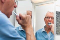 Hombre mayor en el espejo que aplica sus dientes con brocha Fotos de archivo libres de regalías