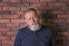 Hombre mayor en el estado de la depresión cerca de la pared de ladrillo Foto de archivo libre de regalías
