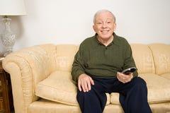 Hombre mayor en el sofá con teledirigido Fotos de archivo libres de regalías