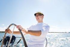 Hombre mayor en el timón en la navegación del barco o del yate en el mar Imagen de archivo
