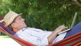 Hombre mayor en hamaca usando el ordenador portátil metrajes