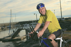Hombre mayor en la bici en la puesta del sol Fotos de archivo