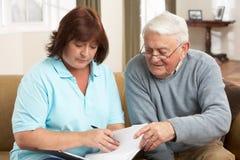 Hombre mayor en la discusión con el visitante de la salud Imagenes de archivo