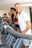 Hombre mayor en la máquina corriente en gimnasia Imágenes de archivo libres de regalías
