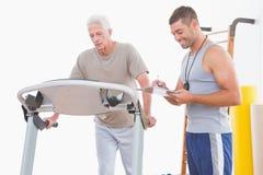 Hombre mayor en la rueda de ardilla con el instructor Foto de archivo libre de regalías