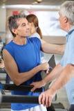 Hombre mayor en la rueda de ardilla en gimnasia foto de archivo libre de regalías