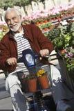 Hombre mayor en la vespa de motor en el jardín Imágenes de archivo libres de regalías