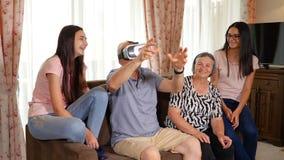 Hombre mayor en las auriculares de la realidad virtual o los vidrios 3d que se divierten metrajes