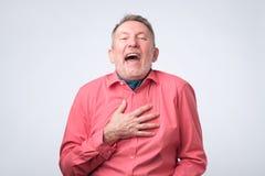 Hombre mayor en las risas rojas de la camisa que llevan a cabo la mano en pecho imagen de archivo