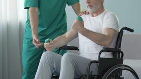 Hombre mayor en pesas de gimnasia de elevación de la silla de ruedas, enfermera por su ayuda lateral, trauma almacen de metraje de vídeo