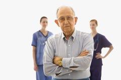 Hombre mayor en primero plano con dos enfermeras en fondo. Fotos de archivo libres de regalías