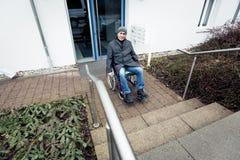 Hombre mayor en silla de ruedas y escaleras imagenes de archivo