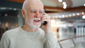 Hombre mayor en suéter en teléfono móvil del uso de la alameda Comprador masculino en centro comercial que habla en el teléfono m almacen de video