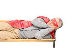 Hombre mayor en traje del super héroe que duerme en banco Fotografía de archivo libre de regalías