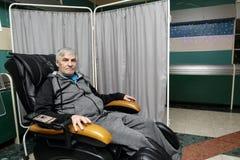 Hombre mayor en una silla del masaje Foto de archivo