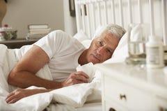 Hombre mayor enfermo en cama en casa Foto de archivo libre de regalías