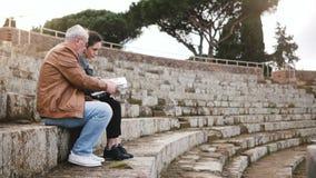 Hombre mayor europeo feliz y mujer joven que se sientan en ruinas viejas del anfiteatro en Ostia, Italia con un mapa y un smartph almacen de metraje de vídeo