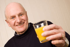 Hombre mayor feliz con el vidrio de jugo Fotografía de archivo libre de regalías