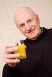 Hombre mayor feliz con el vidrio de jugo Fotografía de archivo