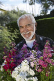 Hombre mayor feliz con las flores en jardín Fotos de archivo