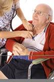 Hombre mayor feliz en sillón de ruedas que controla vitals Fotos de archivo