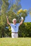 Hombre mayor feliz que celebra jugando a golf Imagen de archivo