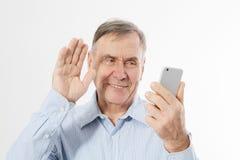 Hombre mayor feliz que habla en el teléfono en el backgrpund blanco El viejo hombre de negocios tiene conversación sobre la charl fotografía de archivo