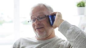 Hombre mayor feliz que invita al smartphone en casa 25 almacen de metraje de vídeo