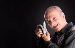 Hombre mayor feliz que muestra dólares Imagen de archivo