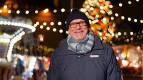 Hombre mayor feliz que sonríe en el mercado de la Navidad metrajes