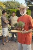 Hombre mayor feliz que sostiene las plantas en conserva Imágenes de archivo libres de regalías