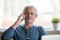 Hombre mayor feliz que tiene conversación agradable del teléfono móvil imagenes de archivo