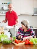 Hombre mayor feliz y mujer madura que hacen tareas Imagen de archivo
