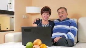 Hombre mayor feliz y una mujer que mira la película en el ordenador portátil Abrazan y discuten qué está sucediendo en la pantall metrajes