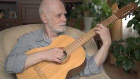 Hombre mayor hermoso apuesto en la camiseta que se sienta en silla en casa y que toca la guitarra almacen de video
