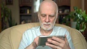 Hombre mayor hermoso apuesto que se sienta en silla en casa Usando smartphone, hojeando, leyendo noticias metrajes