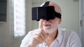 Hombre mayor hermoso en blanco usando VR 360 vidrios en casa Haciendo hojee, enfoque y golpee ligeramente los gestos almacen de metraje de vídeo