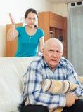 Hombre mayor infeliz con la esposa enojada Foto de archivo