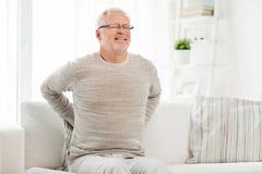 Hombre mayor infeliz que sufre de dolor de espalda en casa Fotos de archivo libres de regalías