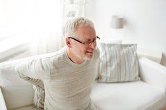 Hombre mayor infeliz que sufre de dolor de espalda en casa Fotografía de archivo