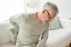 Hombre mayor infeliz que sufre de dolor de espalda en casa Imágenes de archivo libres de regalías