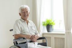 Hombre mayor inhabilitado sonriente en una silla de ruedas solamente en casa fotos de archivo libres de regalías