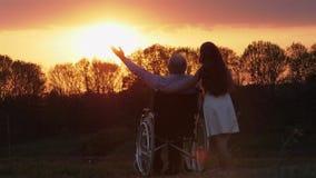 Hombre mayor inválido en la puesta del sol con la nieta