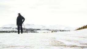 Hombre mayor irreconocible que disfruta de la visión, paisaje nevado, Edimburgo Imagen de archivo